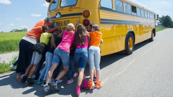 Als der Bus nicht mehr anspringt, muss die gante TanzAlarm-Crew mit anschieben.    Rechte: KiKA/MingaMedia