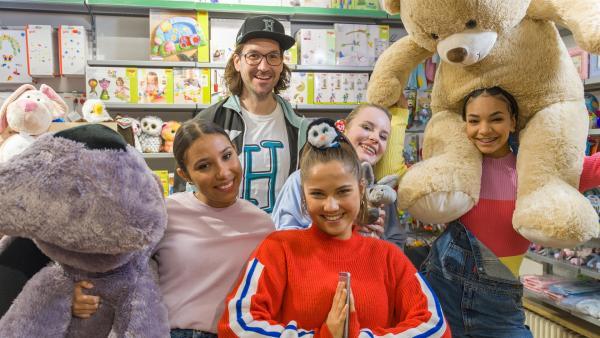 Die TanzAlarm Kids und herrH suchen im Spielzeugladen nach dem richtigen Geschenk. | Rechte: KiKA/MingaMedia/Ron Bergmann