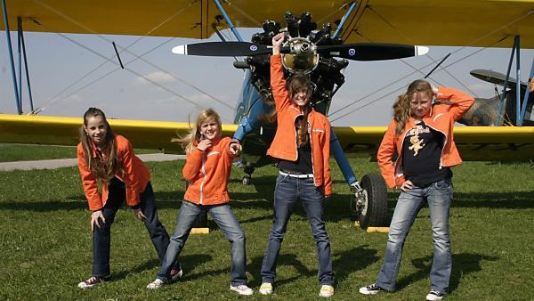 Die Tanzalarm-Kids sind auf dem Flugplatz zu Gast. Tom präsentiert den Beruf des Piloten. | Rechte: Ki.KA/Ilona Kolar