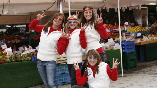 Die Tanzalarm Kids auf dem Münchner Viktualienmarkt als Flower-Power-Girls (v.li.: Ana, Patrizia, Kinga, Rachel hockend) rocken sie den ganzen Platz. | Rechte: Ki.KA/Ilona Kolar
