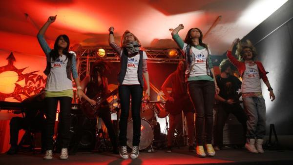 Die Kids lassen sich die tollsten Luftgitarren von den Profis zeigen. Und dann rocken sie richtig drauf los! | Rechte: Ki.KA/ZDF/Ilona Kolar
