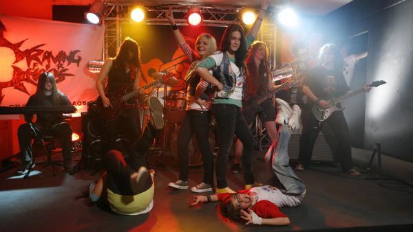 Es wird laut und es wird wild!! Heavy Metal - Luftgitarre, durcheinander fliegende lange Haare, laute Musik Heute beweisen die TA-Kids, dass sie sich, im Gegensatz zu Alex, bei echten Rockern beweisen können! | Rechte: Ki.KA/ZDF/Ilona Kolar