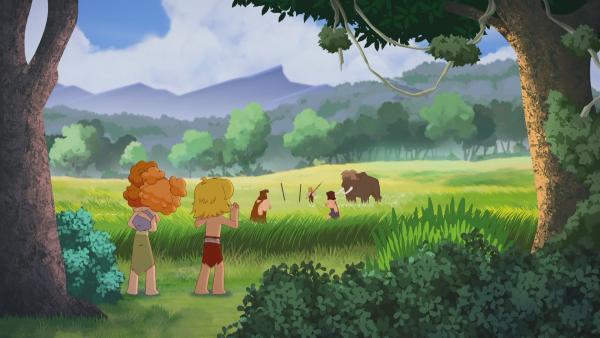 Tib, Tara und Kori schreien laut, um das Mammut zu verjagen. Sie wollen verhindern, dass die Männer die Mammutmutter verletzen.   Rechte: KiKA/hr/TF1/GO-N Productions