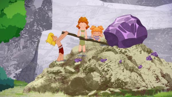 Gemeinsam mit Tara und Kori will Tib den Stein in einen Krater rollen, damit er Tumtum nicht mehr gefährlich werden kann.   Rechte: KiKA/hr/TF1/GO-N Productions
