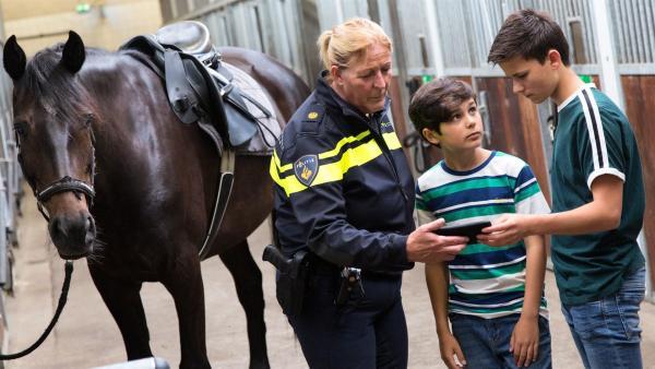 Boris und Milan recherchieren bei den unerschrockenen Pferden der berittenen Polizei und zeigen ihr Video. | Rechte: NDR/NTR/Ketnet 2019