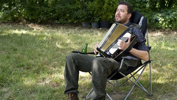 Vinzenz Grieshaber (Michael Sideris) spielt Akkordeon am See. | Rechte: SWR/Maria Wiesler