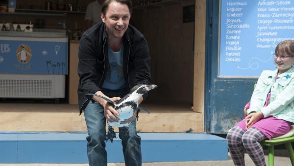 Der Eisdielenbesitzer Peter Wolf (Andt Schwering-Sohnrey) will mit seinem mit Pinguin Cooper Kinder anlocken. | Rechte: SWR/Maria Wiesler