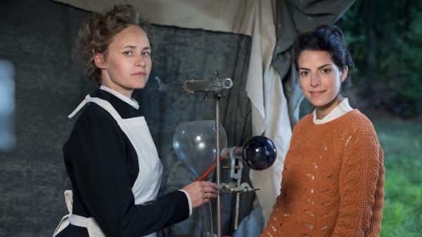 Clarissa (re.) erfährt von Marie Curie (Inez Bjørg David, li), wie ihre Röntgengeräte funktionieren. | Rechte: KiKA/Sabine Finger