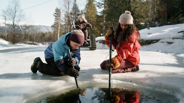 Simon (Oskar Lindquist) , Lars (Björnar Lysfoss Hagesveen) und Nora (Naomi Hasselberg Thorsrud) suchen im zugefrorenen Flussbett nach einem lange verschollenen Medaillon. | Rechte: NDR/NordicStories