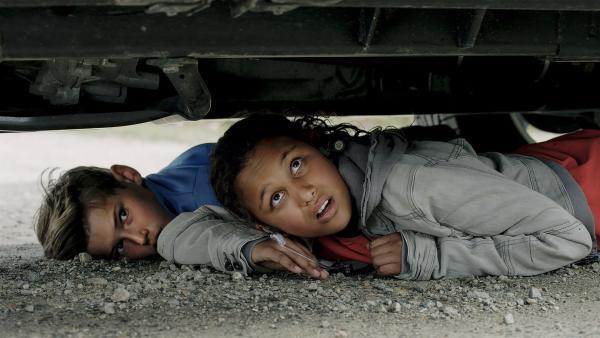 Nora (Naomi Hasselberg Thorsrud) und Simon (Oskar Lindquist) verstecken sich unter Tom und Julias Geländewagen. | Rechte: NDR/NordicStories