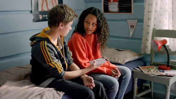 Kristoffer (Vinjar Pettersen) schenkt der erstaunten Nora (Naomi Hasselberg Thorsrud) ein wertvolles Smartphone. Woher hat er nur das Geld dafür? | Rechte: NDR/NordicStories