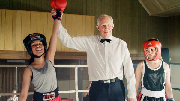 Nora (Naomi Hasselberg Thorsrud, links) gewinnt spielend die ersten Runden im Boxwettkampf. Doch dann brechen die ersten Sportler zusammen. | Rechte: NDR/NordicStories