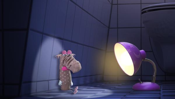 Es ist dunkel und die kleine Lampe hört ein leises Stimmchen. Im Bad findet sie ein einsames Söckchen, das sich beim Versteckspiel so gut versteckt hatte, dass es nicht gefunden wurde. Wo mag nur das andere Söckchen sein?    Rechte: rbb/Bastei Media