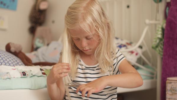Vilda (Sofia Sittnikow) schneidet eine Haarsträhne ab, die sie beim Malen gestört hat.   Rechte: KiKA/Anton Tevajärvi