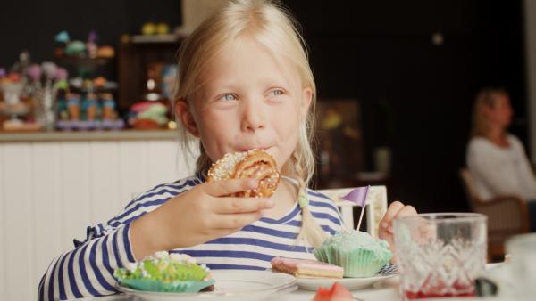 Im Café isst Vilda (Sofia Sittnikow) erst etwas Gesundes, dann häuft sie sich Törtchen auf den Teller. | Rechte: KiKA/Anton Tevajärvi