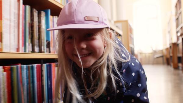 Vilda (Sofia Sittnikow) versteckt sich in der Bibliothek vor ihrem Vater. | Rechte: KiKA/Anton Tevajärvi