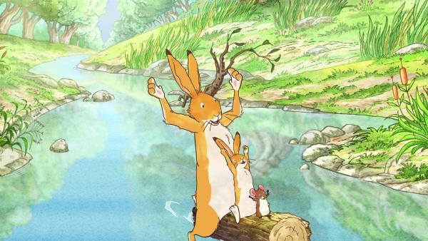 Der große und der kleine kleine braune Hase sowie die kleine Feldmaus schwimmen auf einem Holzstamm den Fluss hinab. | Rechte: KiKA/SLR Productions Australia Pty.Ltd./Scrawl Studios Pte Ltd./hr/ARD