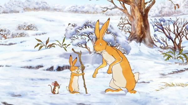Der kleine braune Hase zeigt dem großen braunen Hasen den Glücksstock, den er gerade im Schnee gefunden hat. | Rechte: KiKA/SLR Productions Australia Pty.Ltd./Scrawl Studios Pte Ltd./hr/ARD