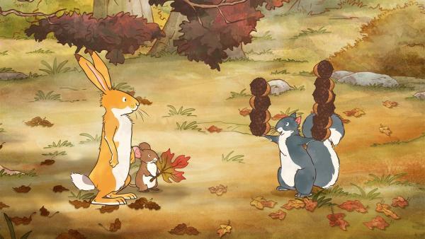 Die kleine Feldmaus freut sich gerade über ihr schönes Blatt als die beiden Freunde Gesellschaft bekommen. Das kleine Grauhörnchen erscheint und trägt eine ganze Menge Eicheln mit sich. Die hat es unterwegs gesammelt. Seine Freude über den tollen Fund verschwindet schlagartig als klar wird, dass diese Eicheln die Wegmarkierung für den Rückweg waren. Wie sollen die drei Freunde nun den Weg zurück zur Wiese finden? | Rechte: KiKA/SLR Productions Australia Pty.Ltd./Scrawl Studios Pte Ltd./hr/ARD