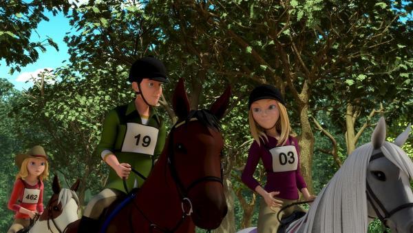 Beim Wanderritt-Wettbewerb starten immer Paare: Vanessa (re.) reitet mit Jerry (li.) zusammen los. Wendy (hinten) kann es nicht fassen, wie sie dabei mit ihm flirtet. | Rechte: ZDF/Wendy and Associated Characters (c) WPL 2012