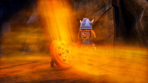 Wickie steht in der Höhle vor einem Schild, von dem ein enormer orange-goldener Lichterglanz ausgeht | Rechte: ZDF