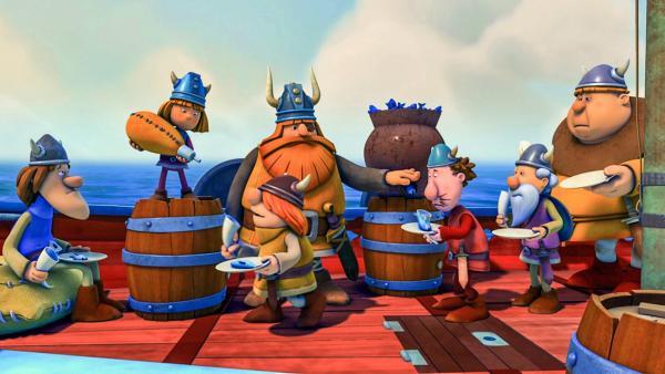 Die Wikiner stehen mit Tellern in der Hand an Bord des Schiffes, wo Halvar jedem einen Fisch austeilt. Wickie schenkt aus einem Schlauch Trinken ein. Alle sehen unglücklich aus. | Rechte: ZDF