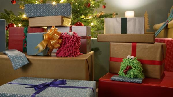 Wisch und Mop stürzen sich begeistert in die Erkundung des weihnachtlichen Glitzers und erklimmen den Geschenkeberg. | Rechte: NDR/Trikk17