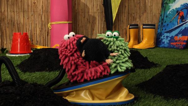 Wisch und Mop sitzen mit einem Maulwurf auf einem Blasebalg und schauen verdutzt | Rechte: Trikk17 Foto: Trikk17
