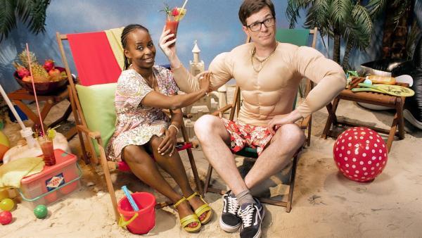 Ralph und Shary sind heute total gut drauf: Im Liegestuhl, mit Sonne, Sand und Meer fühlen sie sich wie im Urlaub. Aber auch im Urlaub schadet es nicht, ab und zu den Kopf anzustrengen. Sie verraten die Bauanleitung für einen entspannenden Sand-Ballon. | Rechte: WDR/Thorsten Schneider