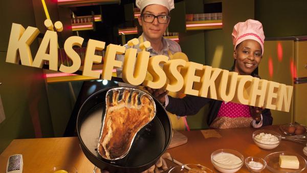 Heute heißt es im Studio: Backschürzen an, Kochmützen auf – und Nase zuhalten! Shary und Ralph backen Käsefüßekuchen. Aber keine Sorge – dieser Kuchen stinkt nicht! Warum er trotzdem so heißt, und wie man ihn herstellt, erfahrt ihr von unseren beiden Hobby-Bäckern. | Rechte: WDR/Thorsten Schneider