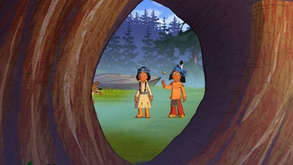 Regenbogen und Yakari versuchen, einen Ball durch das Loch im Baum zu werfen.   Rechte: WDR/Storimage