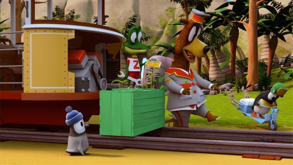 """Zacki will die Bahn schneller machen und dafür ein """"Beschleunigungsteil"""" im Motor montieren. Jonathan und Kurti, die beiden Pinguine, finden dieses gelbe """"Beschleunigungsteil"""" interessant. Ob das auch in ihre Roller passen würde?   Rechte: ZDF/Grid Animation, TELEGAEL"""