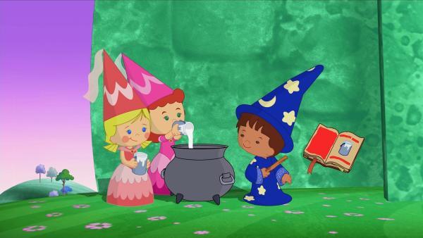 Zoé und Tanja mischen mit Zauberer Finns Hilfe aus dem großen Zauberbuch rosa Farbe. | Rechte: KiKA/Mike Young Productions