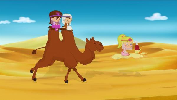 Lili und Max reiten auf Kamel Asif. Zoé fliegt mit ihrme fleigenden Teppich QuackQuack voraus.   Rechte: KiKA/Mike Young Productions