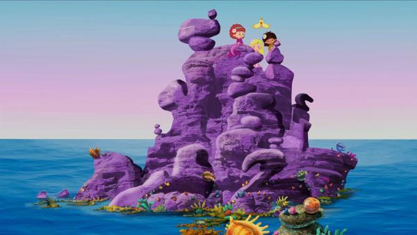 Hier sitzen Tanja, Zoé und Yasemin gemeinsam mit QuackQuack auf einem lila Felsen, der zu Tanjas Meer gehört. | Rechte: KiKA/Mike Young Productions