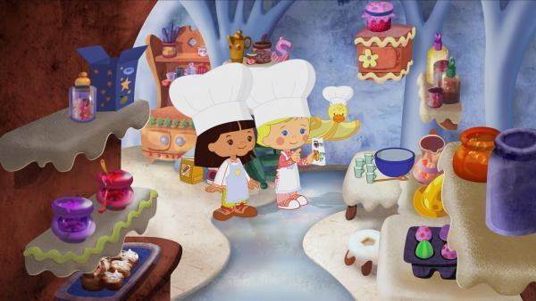 Diesmal sind Yasemin, Zoé und QuackQuack im Zuckerbäckerland gelandet und gerade dabei einen Kuchen zu backen. | Rechte: KiKA/Mike Young Productions