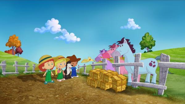 Tanja, Zoé, Hofhund Freddie und Finn füttern die Pferde mit Stroh. | Rechte: KiKA/Mike Young Productions
