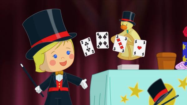 Mit QuackQuack führt Zoé einen Kartentrick vor. | Rechte: KiKA/Mike Young Productions