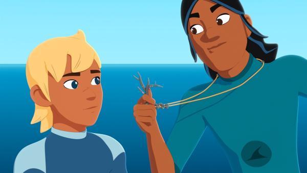 Auru (r.) zeigt Yann (l.) stolz seinen neuen Anhänger aus schwarzer Koralle, den ihm seine Eltern geschenkt haben, weil er sich in letzter Zeit so verantwortungsvoll gezeigt hat. | Rechte: ZDF/Media Valley/Marzipan Films