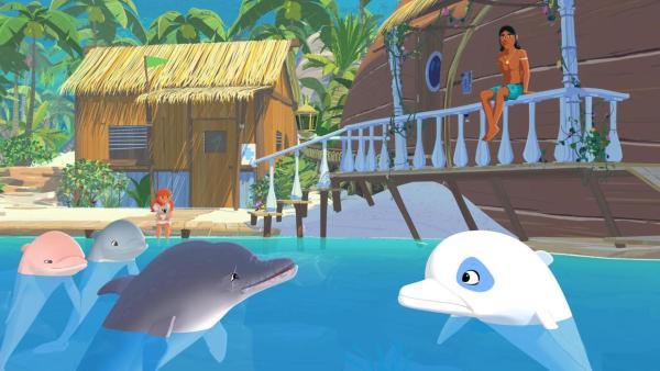 Im Wasser vor zwei Holzgebäuden schwimmen vier Delfine, darunter Zoom. Sie scheinen sich zu unterhalten. Auf der Veranda des einen Gebäudes sitzt Auru und beobachtet die Tiere, Marina sitzt weiter entfernt auf einem Bootssteg und schaut ebenfalls zu den Delfinen. | Rechte: (c) Media Valley / Marzipan Films - 2020