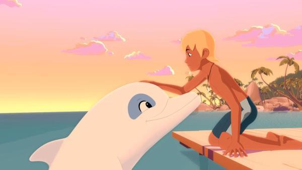 Yann kniet auf einem Bootssteg und streicht dem vor ihm aus dem Wasser schauenden Delfin Zoom glücklich über den Kopf. Auch Zoom lächelt erfreut zu Yann hoch. Im Hintergrund sind Felsen und Bäume der Inselbucht zu sehen. Ein rötlicher Abendhimmel beleuchtet die Szenerie. | Rechte: (c) Media Valley / Marzipan Films - 2020