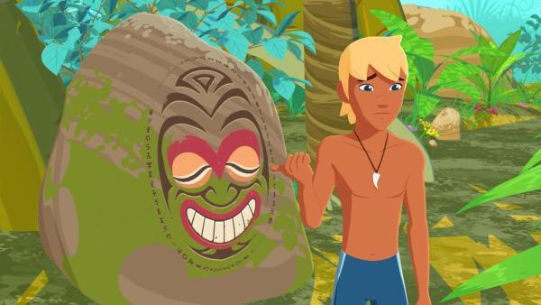 Yann steht schräg vor einem großen Stein, auf dem ein grinsendes Gesicht abgebildet ist. Yann zeigt mit dem Daumen seiner rechten Hand hinter sich auf das Gesicht. Hinter dem Stein und Yann sind Pflanzen und Bäume zu sehen. | Rechte: (c) Media Valley / Marzipan Films - 2020