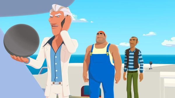 Van Krook (links) hält die schwarze Perle Poemari in der Hand und hält mit der anderen Hand sein Telefon an seinen Kopf. Ganoven Biff und Rico (beide mittig) stehen hinter ihm auf der Jacht. | Rechte: Media Valley/Marzipan Films - 2020