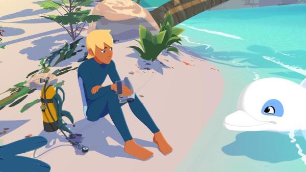 Yann (links) sitzt am Strandufer, hält eine Videokamera in der Hand und schaut zu Zoom (rechts) herüber. | Rechte: Media Valley/Marzipan Films - 2020